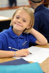 Elementary girl sitting at table smiling holding pencil
