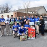 High school students holding gifts standing together outside with Mrs. Eifert