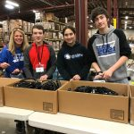 Students and teacher smiling serving packaging boxes in warehouse