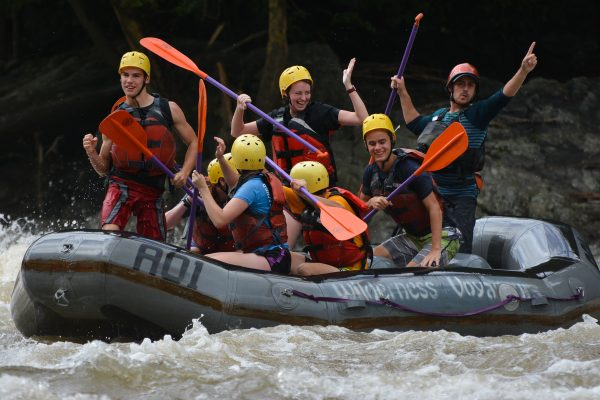 Group of students with helmets on raft having fun in rapids
