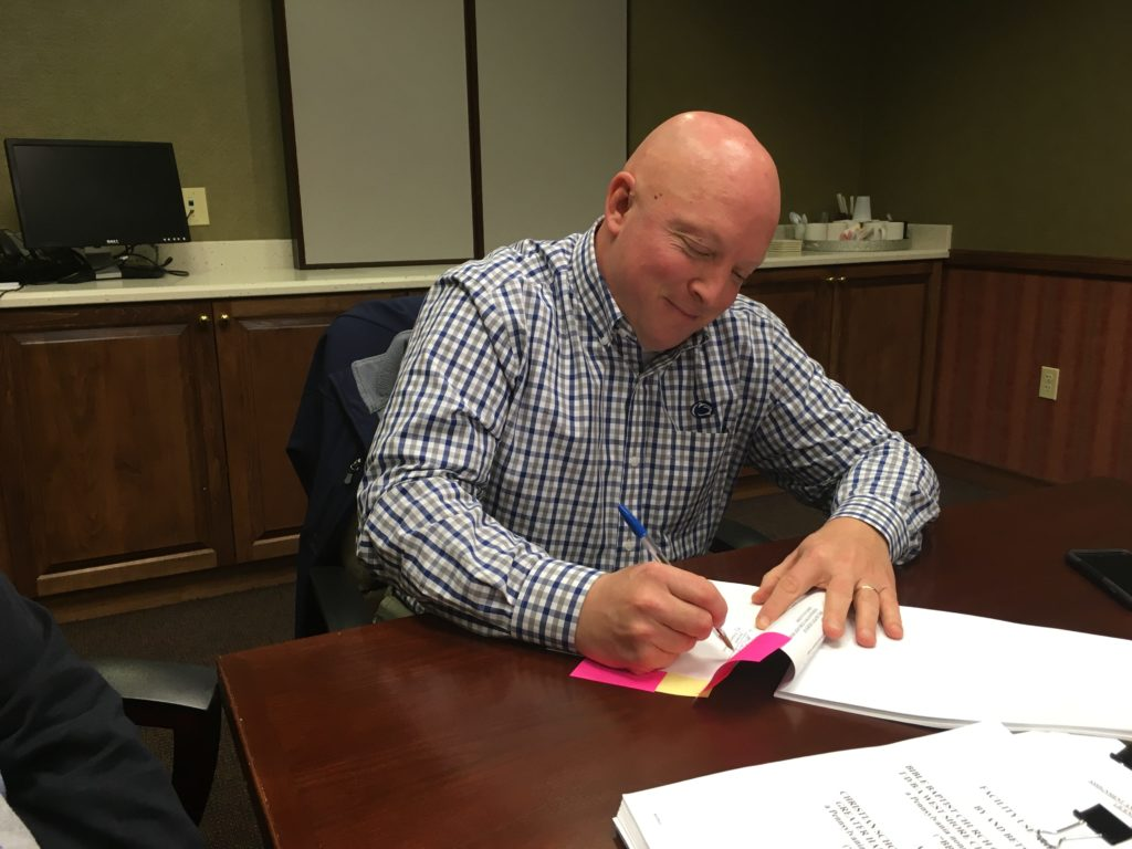 man signing papers at a table