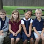 Elementary students on bench in uniform