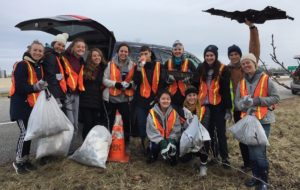 Students doing trash removal in community with orange vests
