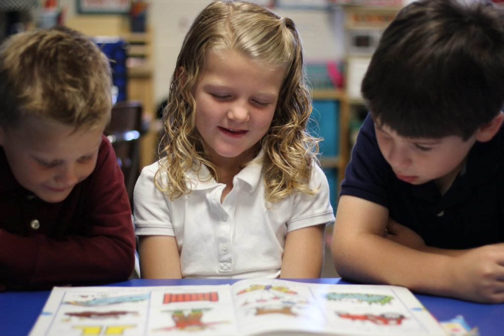 elementary students sitting at a table reading a book
