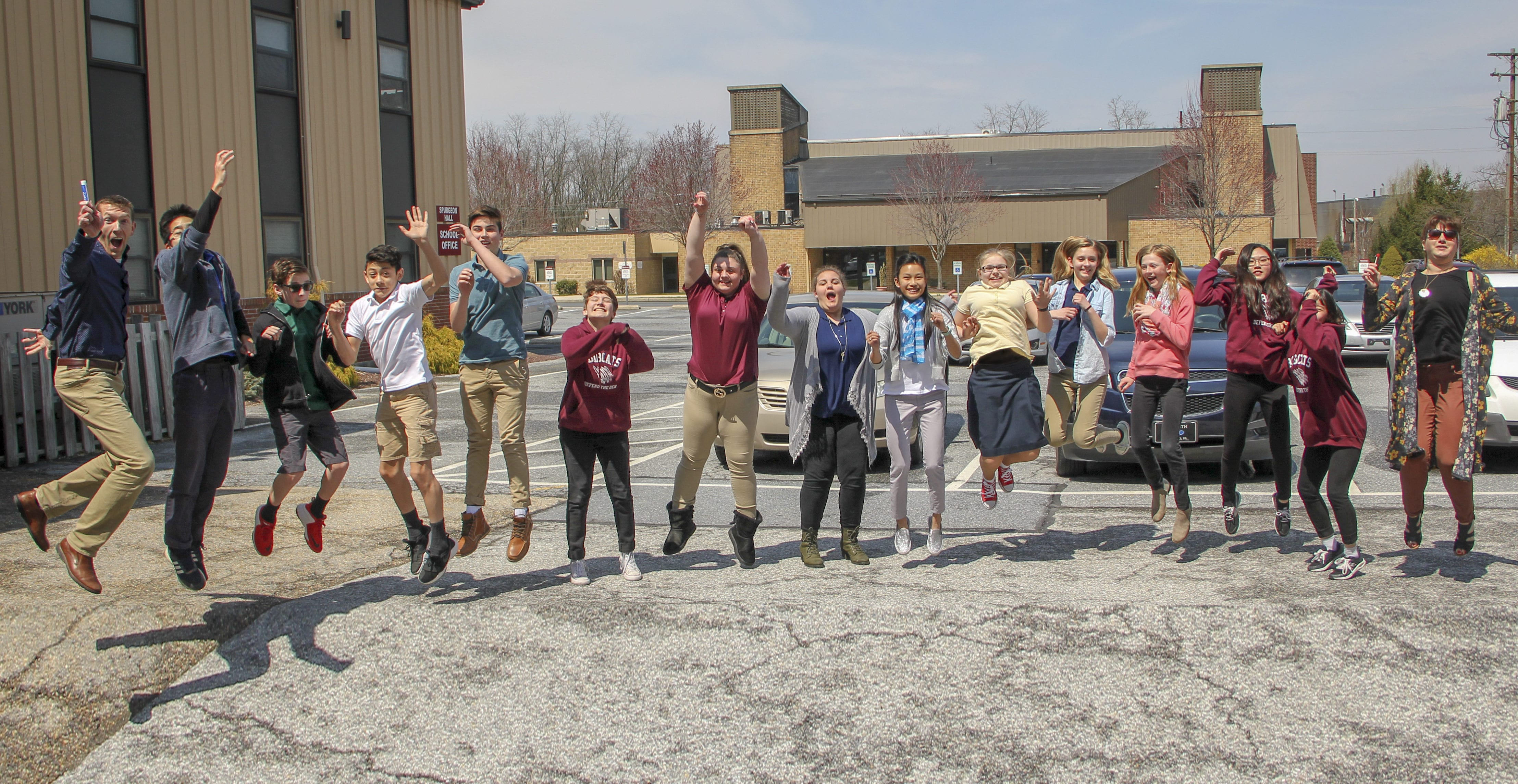 jumping students and teacher in parking lot