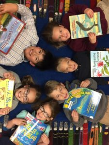 Six WSCA elementary students holding books while lying down in circle