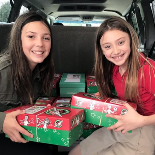 students holding boxes for christmas shoebox collection